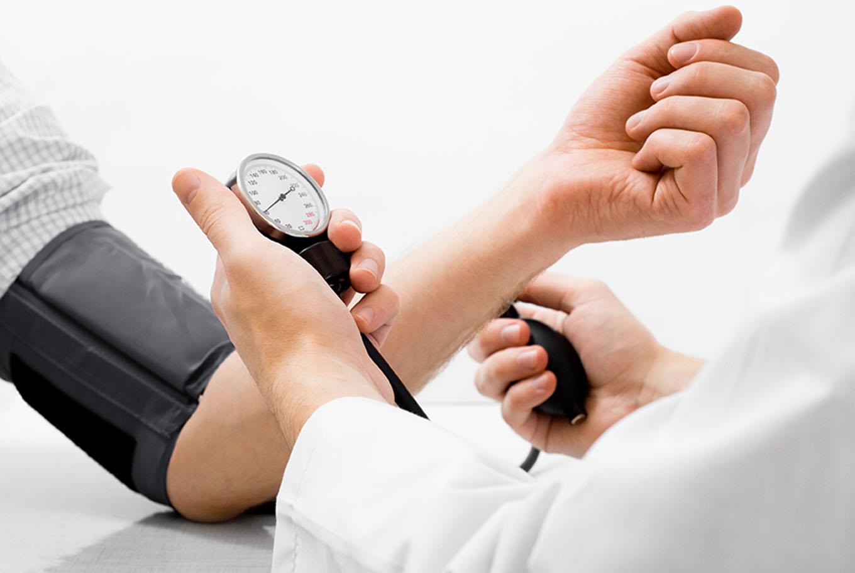 Doctor measuring blood pressure - studio shot on white background