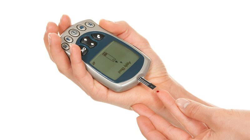 Diabetes measurement glucose sugar level blood test for diabetic patient using new smart glucometer test isolated on a white background