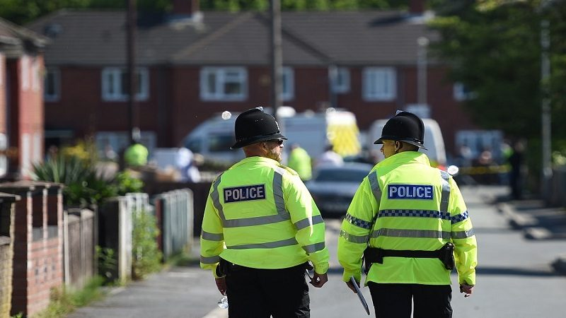 Police officers stand on duty on a cordoned-off road in Fallowfield, Manchester, in northwest England on May 23, 2017, as they search a nearby resdiential property following the May 22 deadly terror attack at the Ariana Grande concert at the Manchester Arena. Twenty two people have been killed and dozens injured in Britain's deadliest terror attack in over a decade after a suspected suicide bomber targeted fans leaving a concert of US singer Ariana Grande in Manchester. / AFP PHOTO / Oli SCARFF