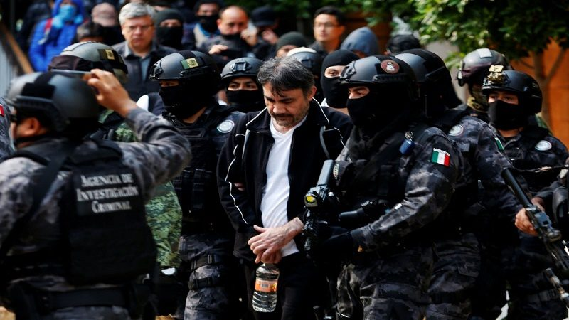 """Accused drug kingpin Damaso Lopez (C), nicknamed """"The Graduate"""",  is escorted by police officers in Mexico City, Mexico May 2, 2017. REUTERS/Carlos Jasso"""