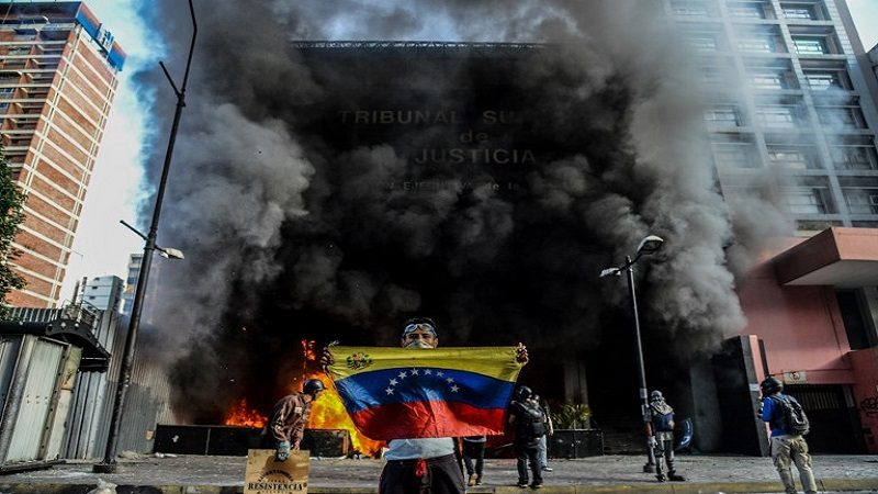 Anti-government demonstrators attack the administration headquarters of the Supreme Court of Justice as part of protests against President Nicolas Maduro in Caracas, on June 12, 2017.  With Venezuelans suffering from high inflation, food shortages and soaring crime rates, plus a deepening corruption scandal, the Venezuelan opposition has mounted near-daily anti-government protests since April 1. The protests have left 66 dead and more than a thousand injured, according to prosecutors.   / AFP PHOTO / Federico PARRA