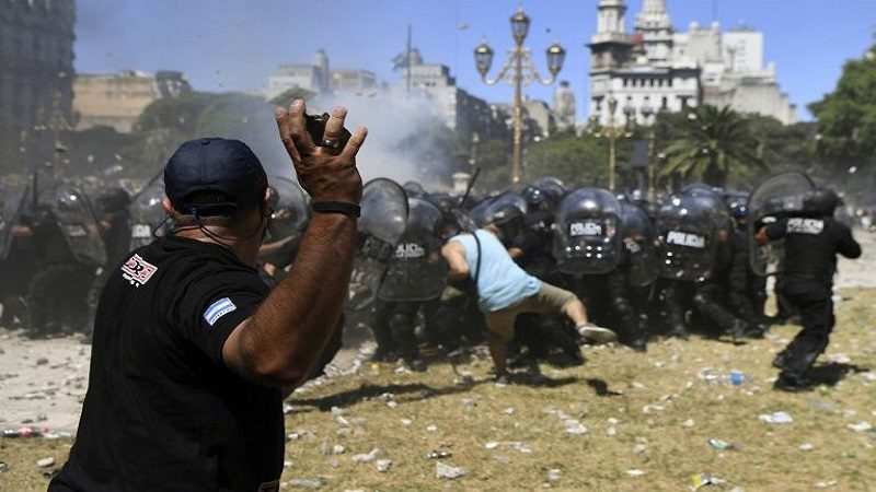 A demontrator hurls stones at riot police during clashes within a protest against the proposed pension reforms outside the Congress in Buenos Aires on December 18, 2017.  Protesters angry at proposed pension and welfare reforms by the center-right government of President Mauricio Macri, lobbed stones, bottles and firecrackers at police, in the second protest in a week to turn violent.  / AFP PHOTO / EITAN ABRAMOVICH
