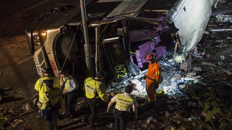 Firefighters sort through crash debris after a bus crash in Hong Kong on February 10, 2018.  The driver of a double-decker bus that toppled over in Hong Kong killing at least 18 people and injuring more than 50 others on February 10 evening has been arrested for dangerous driving, police said. / AFP / ISAAC LAWRENCE