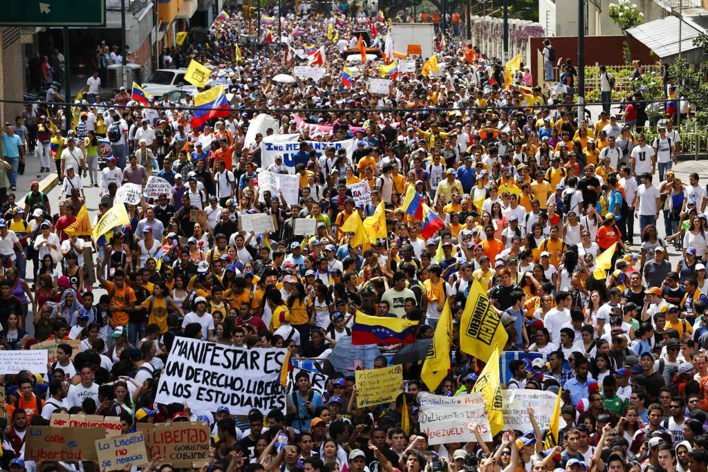 Opposition supporters demonstrate against Venezuela's President Nicolas Maduro's government in Caracas February 12, 2014. Armed pro-government groups attacked and shot at people protesting against Maduro's government late on Tuesday in the Andean city of Merida in western Venezuela, injuring five, activists said. REUTERS/Jorge Silva (VENEZUELA - Tags: POLITICS CIVIL UNREST)