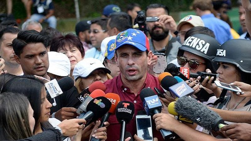 Opposition leader Henrique Capriles speaks to the press at a polling station in Caracas on July 16, 2017 during an opposition-organized vote against Venezuelan President Nicolas Maduro's plan to rewrite the constitution. Authorities have refused to greenlight the vote that has been presented as an act of civil disobedience and supporters of Maduro are boycotting it. Protests against Maduro since April 1 have brought thousands to the streets demanding elections, but has also left 95 people dead, according to an official toll.  / AFP PHOTO / Federico PARRA