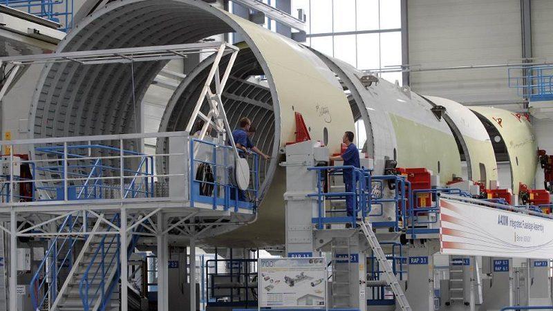 Mitarbeiter des Flugzeugsherstellers Airbus besehen sich am Montag, 24. Juli 2006 in Bremen eine neue Anlage fuer die integrierte Rumpfmontage des  Airbus A400M. Airbus startet ab sofort mit der Rumpfmontage des A400M, dem modernsten militaerischen Transportflugzeug. Der Rumpf besteht aus vier Sektionen, die in verschiedenen Werken gefertigt und in Bremen zusammengefuegt werden. 192 Militaerflugzeuge sind bereits bestellt.  (AP Photo/Kai-Uwe Knoth) -- Workers take a look at a new integrate fuselage assembly unit in Bremen,  northern Germany on Monday, July  24, 2006. Airbus starts the final assembly of the fuselage for the A400M which consist of four parts coming from different factories in Europe in Bremen. The A400M is the newest military cargo airplane, Airbus has already 192 orders. (AP Photo/Kai-Uwe Knoth)